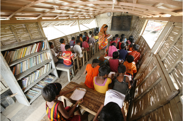 Students it in a classroom on a boat while their teacher reads to them