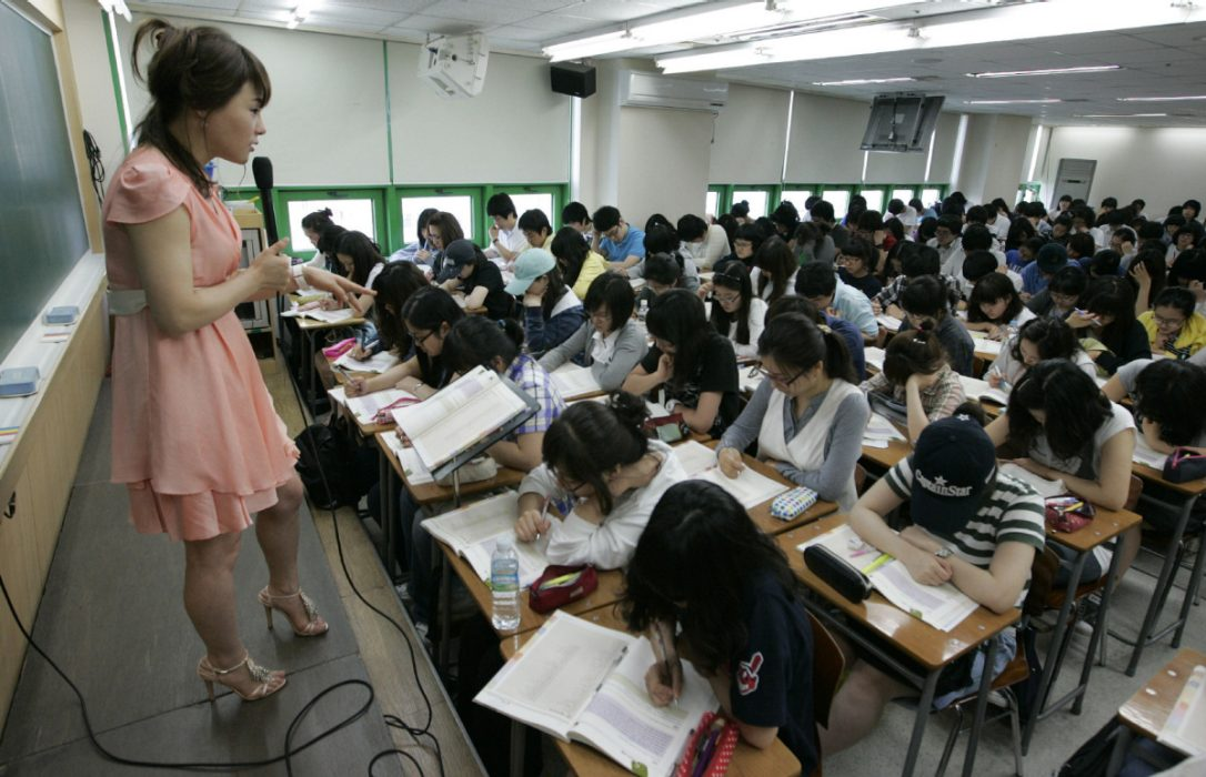 Korean teacher at a microphone teaching a room full of students